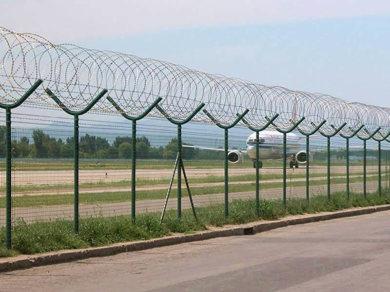 Concertina razor wire is installed onto the Y post of the welded mesh fence in an airport.