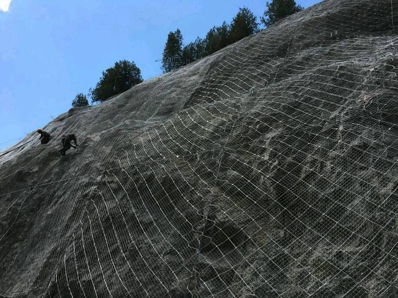 Steel wire rope net with chain link mesh installed on the mountain surface.