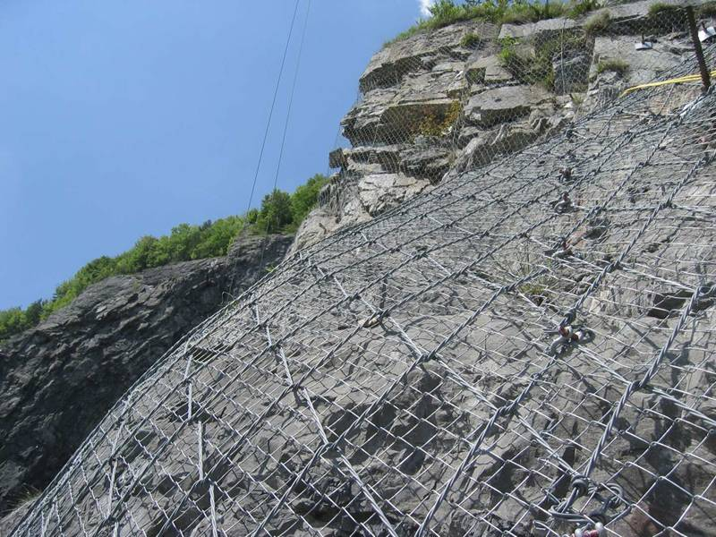 Spider spiral rope mesh with chain link mesh as an active rockfall barrier system.
