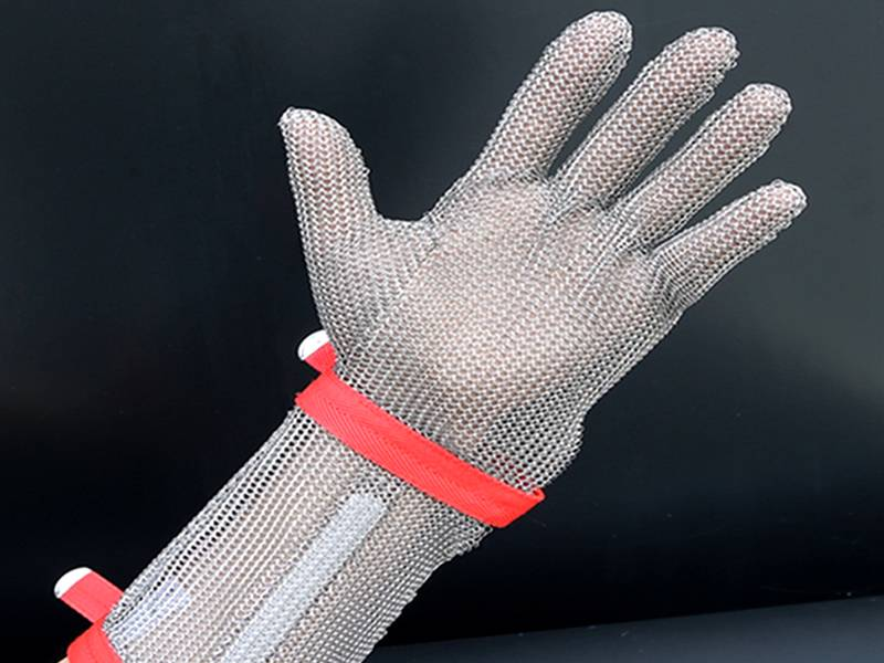 A long-cuff chainmail glove with red fastening strap resistant to a knife cut.