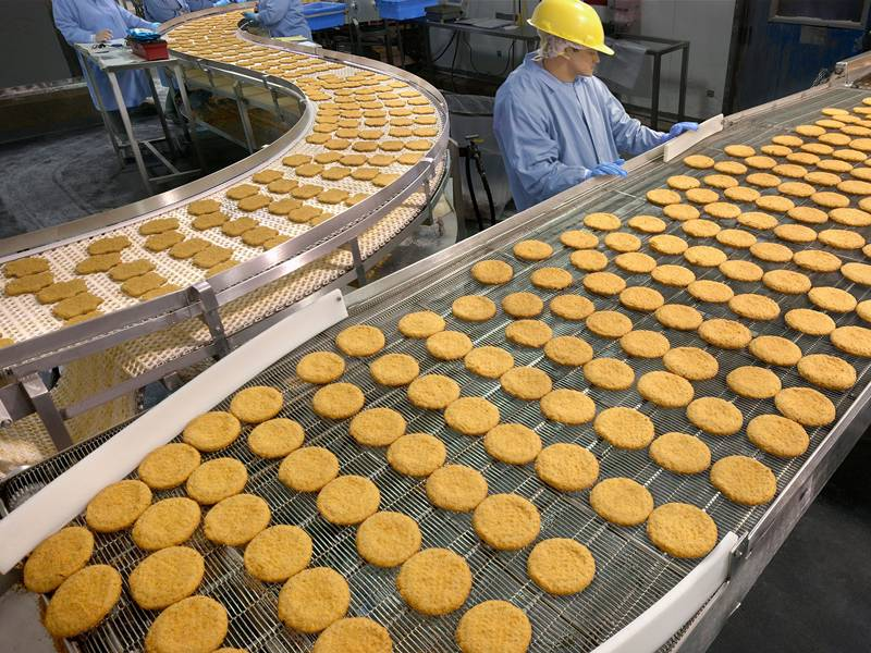 A man is working beside flat flex conveyor belt which full of biscuit.