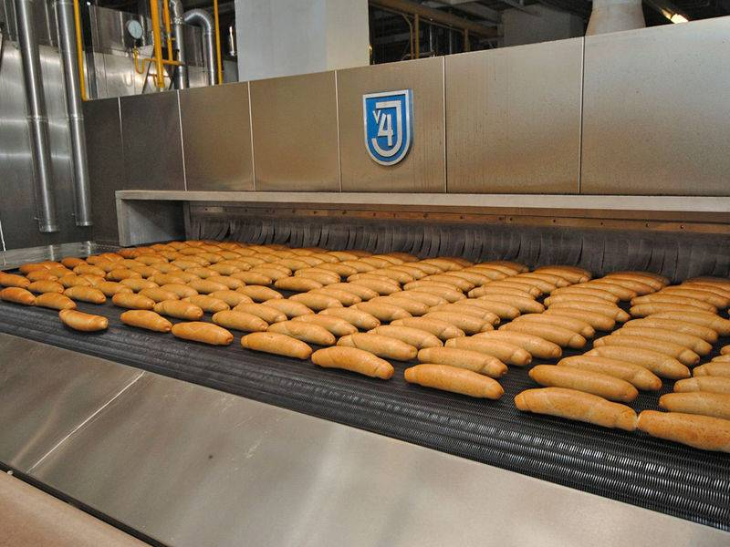 Several bar bread neatly placed on the dense flat spiral conveyor belt.