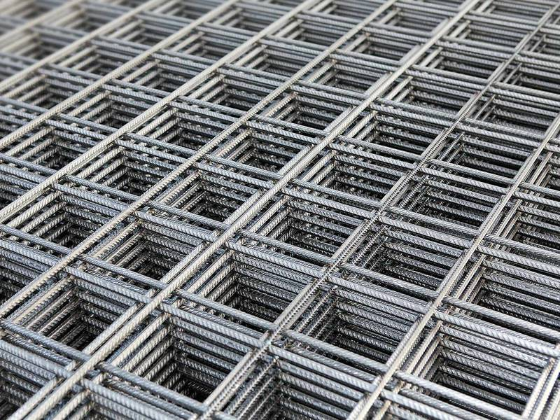 Many galvanized square concrete reinforcing mesh sheets placed together orderly.