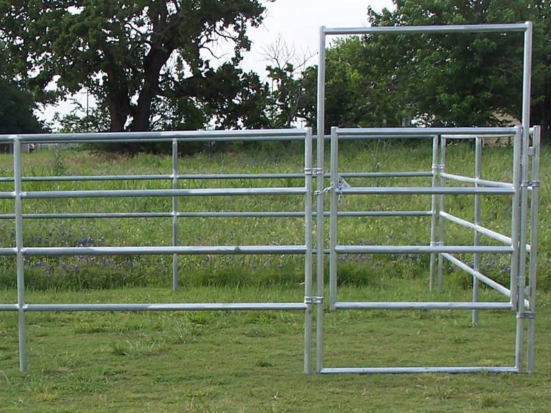 A galvanized horse fence with a gate placed on the grassland.