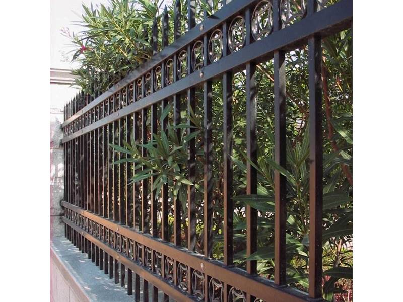 Black galvanized steel tubular fence with decorative ring installed on concrete wall.