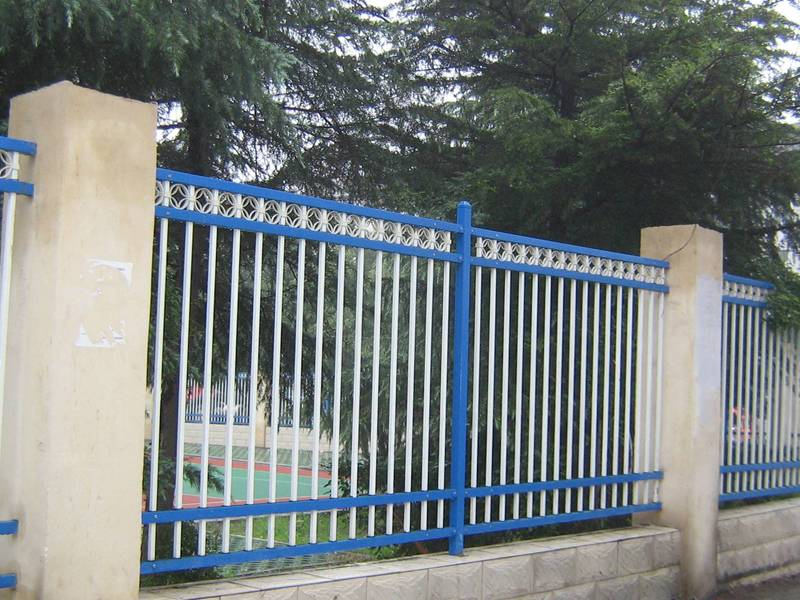 Blue and white flat-top galvanized steel tubular fence with decorative ring installed on concrete wall.