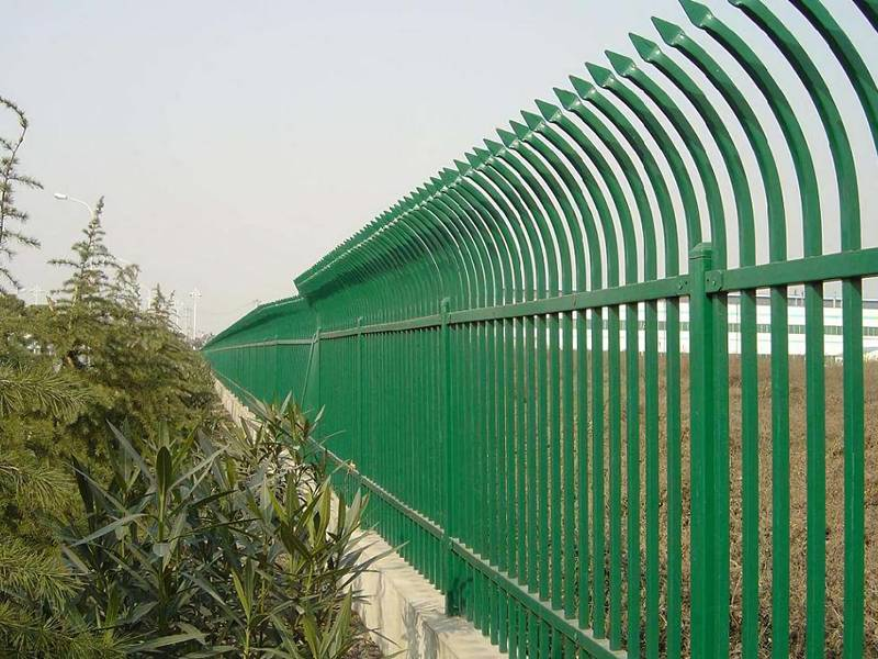 A close-up picture of green hot-dip galvanized steel picket fence with single curved top.