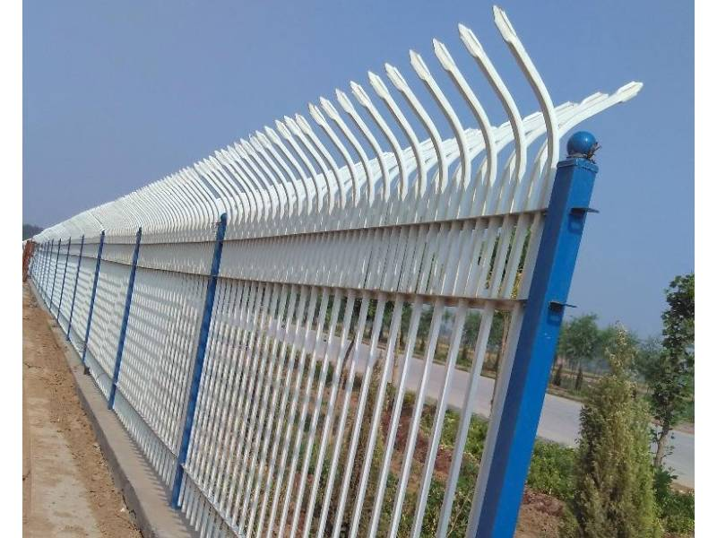 Blue and white double cranked top galvanized steel tubular fence installed by the side of the road.