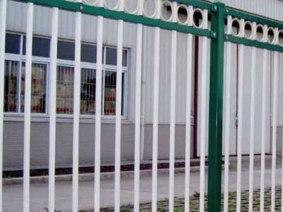 Green and white garrison steel tubular fence with flat top installed on the concrete wall.