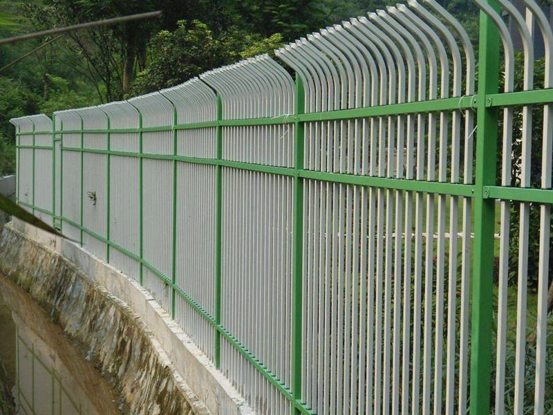 Green and white curved-top galvanized steel tubular fence with installed by the drainage ditch.