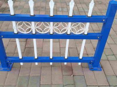 Blue and white garrison galvanized steel tubular fence with spear top and decorative ring.