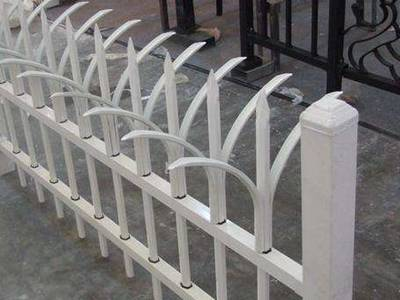 White garrison galvanized steel tubular fence with two-way cranked top and spear point pickets.