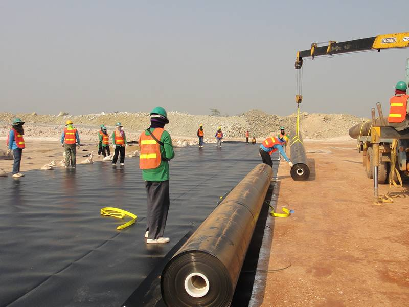 Many workers are setting the geomembrane in ground.