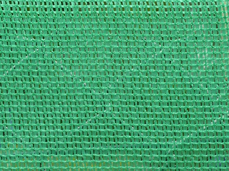 Green knitted windbreak netting installed on chain link fence for court fencing.