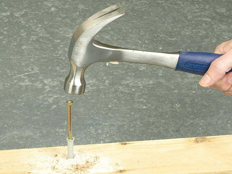A people is knocking the smooth shank nails in a board with hammer.