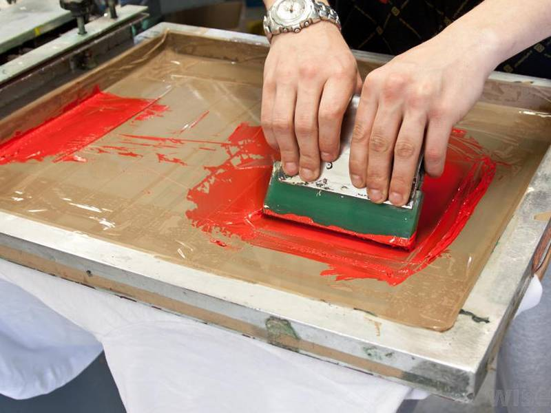Two hand is holding the squeegee for printing on nylon printing screen.
