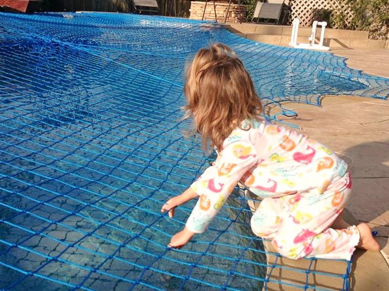 A girl is lying on the blue personal safety net which covering on the swimming pool.