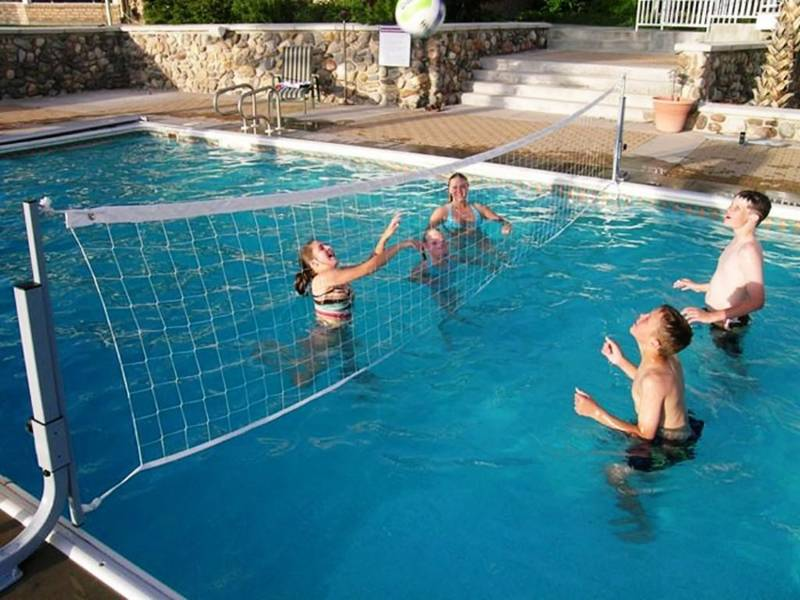 Two men and two women are playing volleyball in the swimming pool.