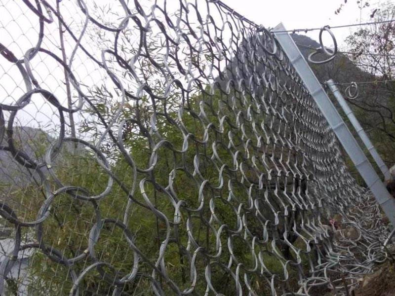 Steel ring net with chain link fence used as a passive mountain rockfall barrier.