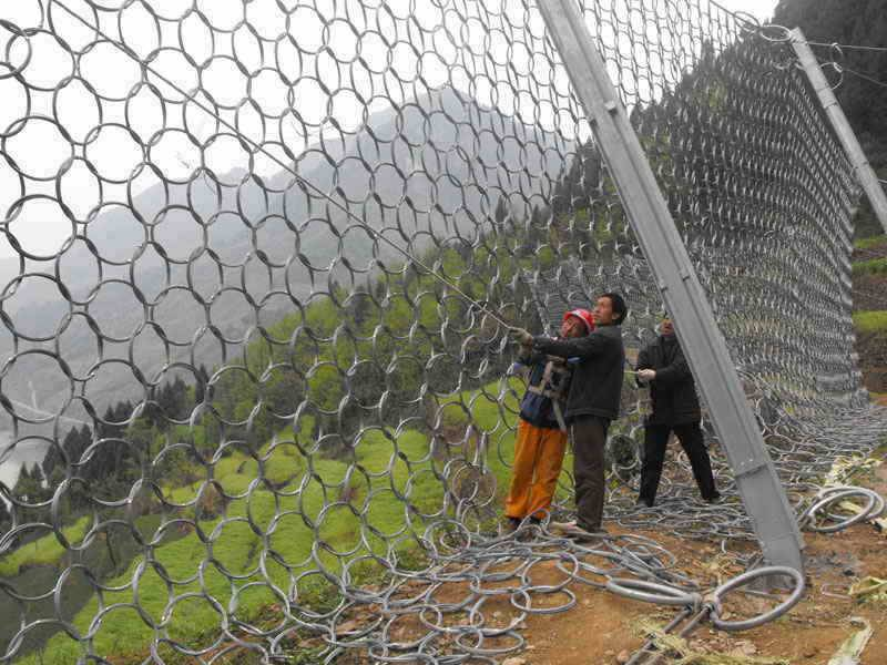 Three workers are installing the steel wire ring net as a passive rockfall barrier.