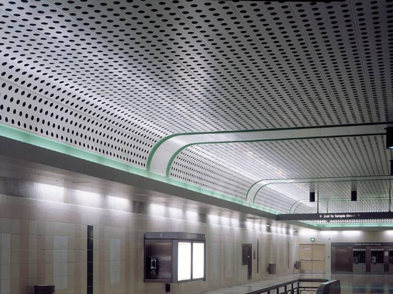 Perforated metal is installed as ceiling in the subway hall.