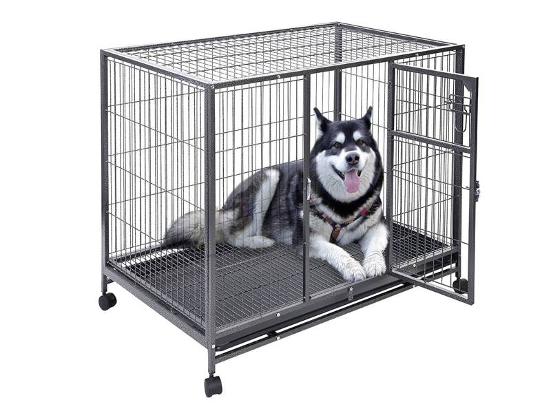 A pet cage with four wheels and a dog is in it.