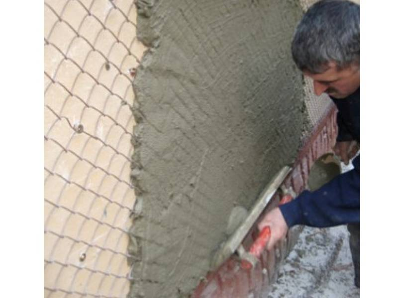 A man plastered a thick layer of cement on the wall with the chain link mesh as reinforcing material.