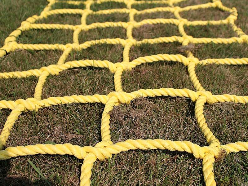A piece of yellow climbing net were placed on the grass.