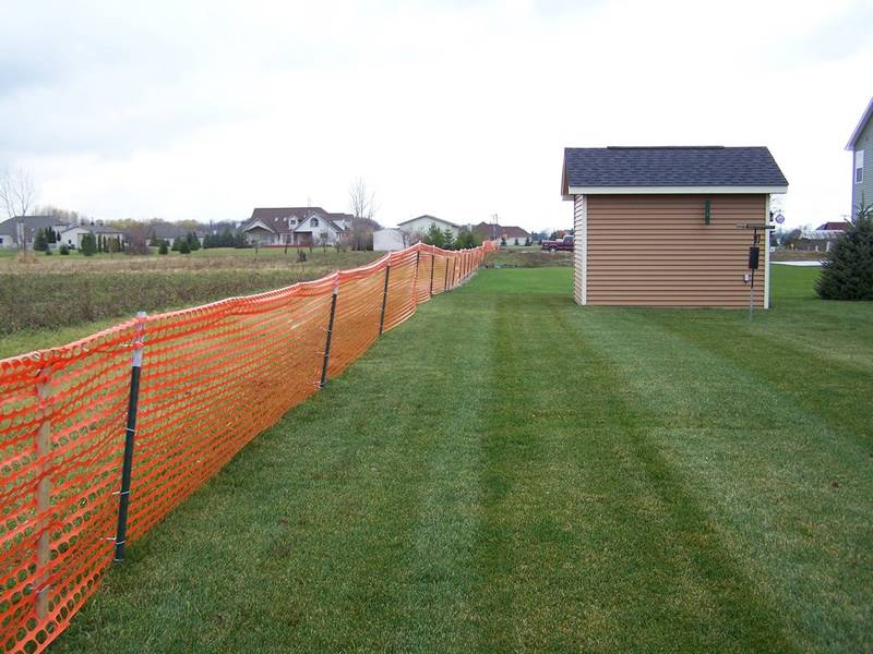 Several pieces of orange safety fence beside a house.