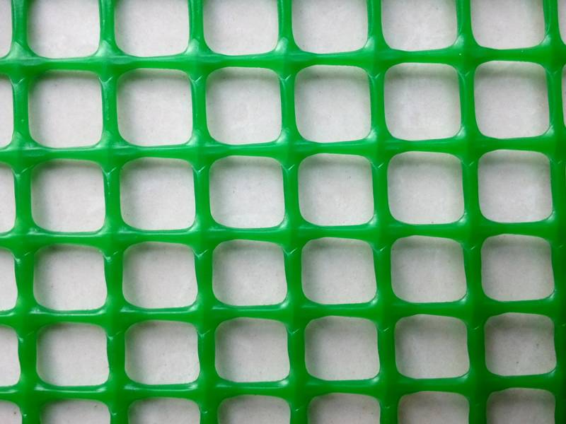 A pieces of green plastic mesh on the white background.