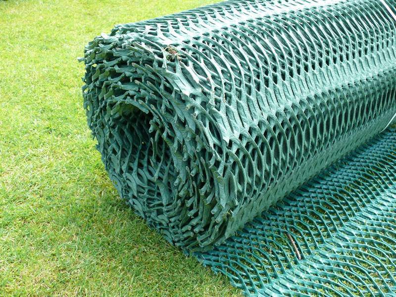 A roll of dark green plastic protective netting on the green grass.