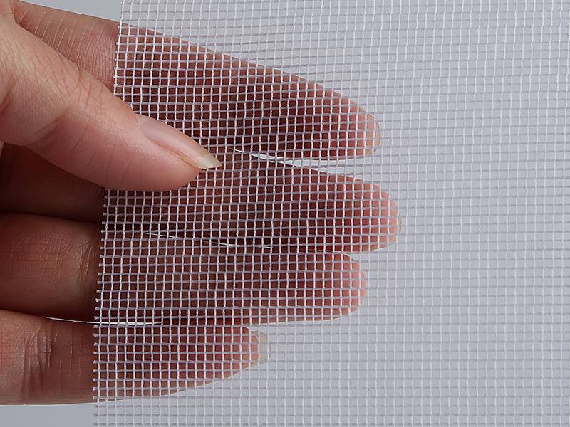 A piece of white polyester mesh window screen sample hold by a hand.