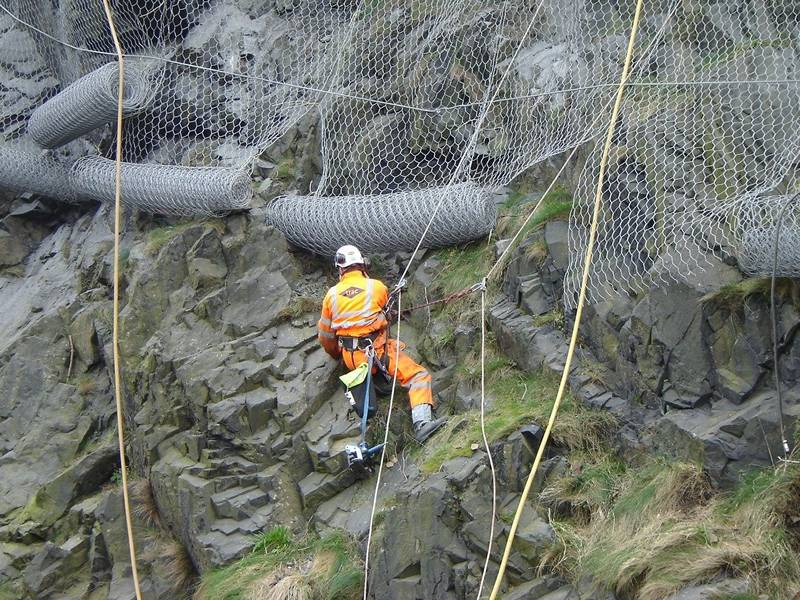 A worker is installing the hexagonal wire mesh for rockfall barrier.
