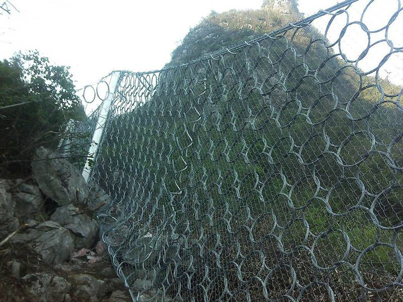 Steel wire ring net combined with chain link fence used as passive rockfall barrier.