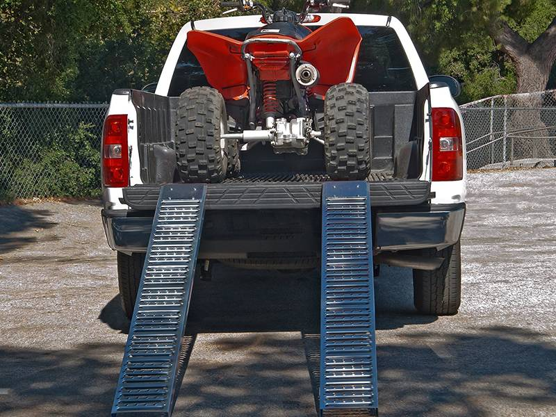 Interlocking safety grating is used as ramps for transporting a small car from a big car.