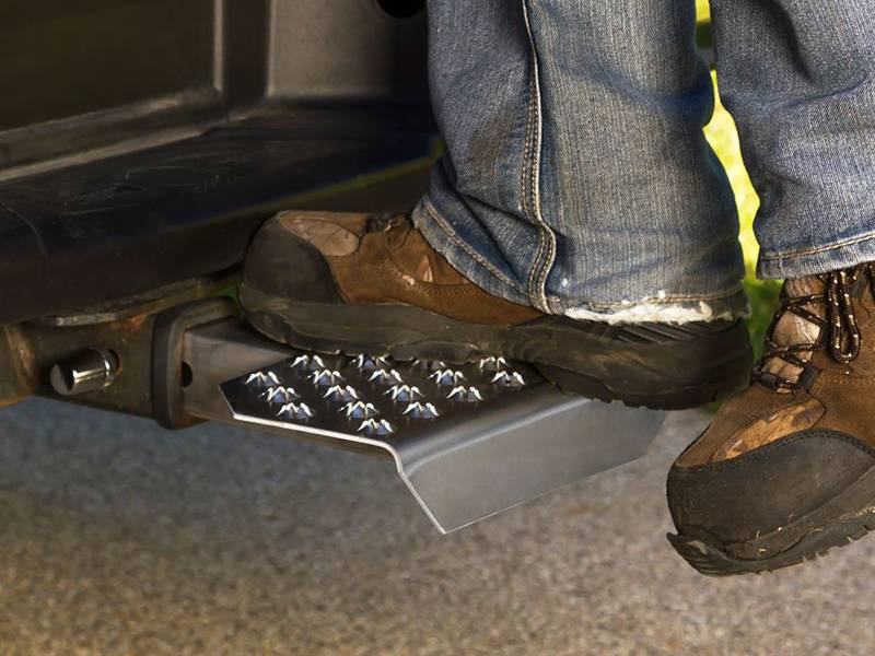 A man is standing on the step that made of traction-grip safety grating.