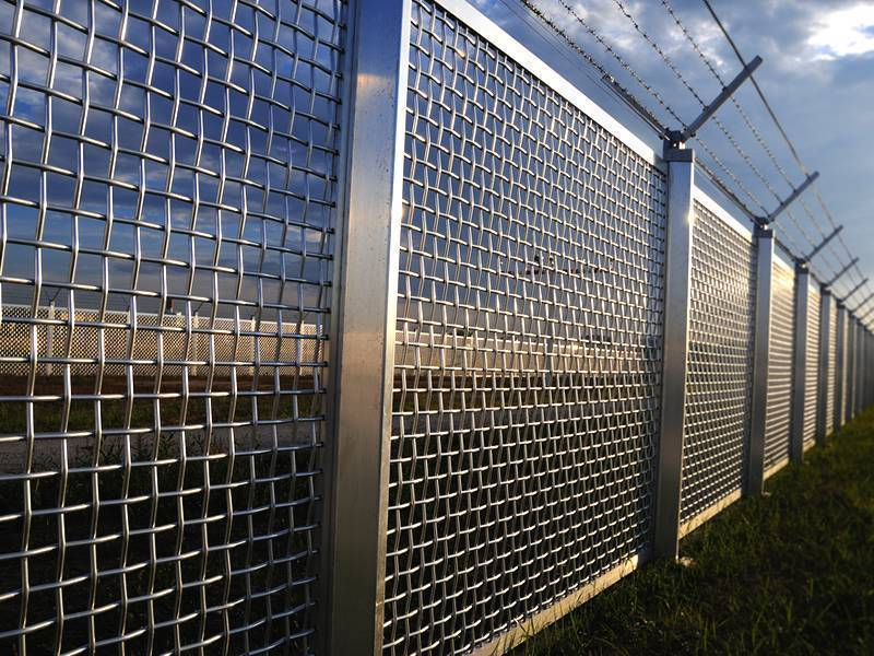 It shows the stainless steel woven wire mesh fence, installed on the green grass.