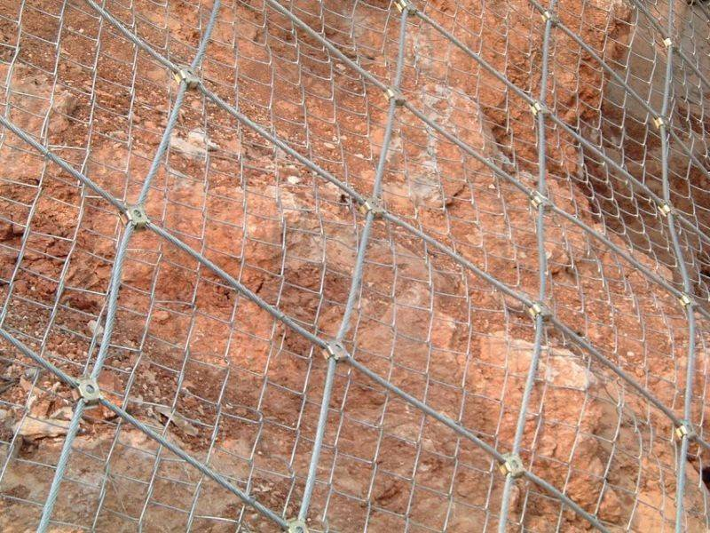 Steel wire rope net with chain link fence as an active rockfall barrier installed on the soil surface.