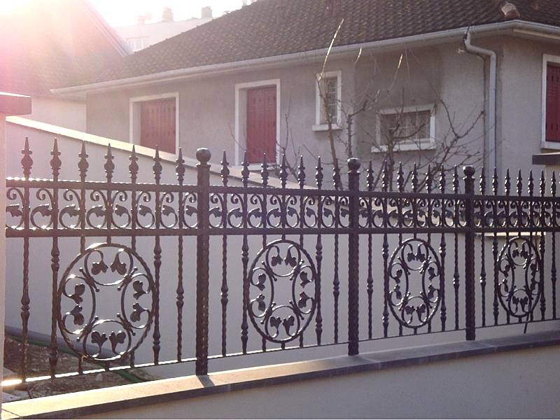 Black patterned wrought iron fence around private house.