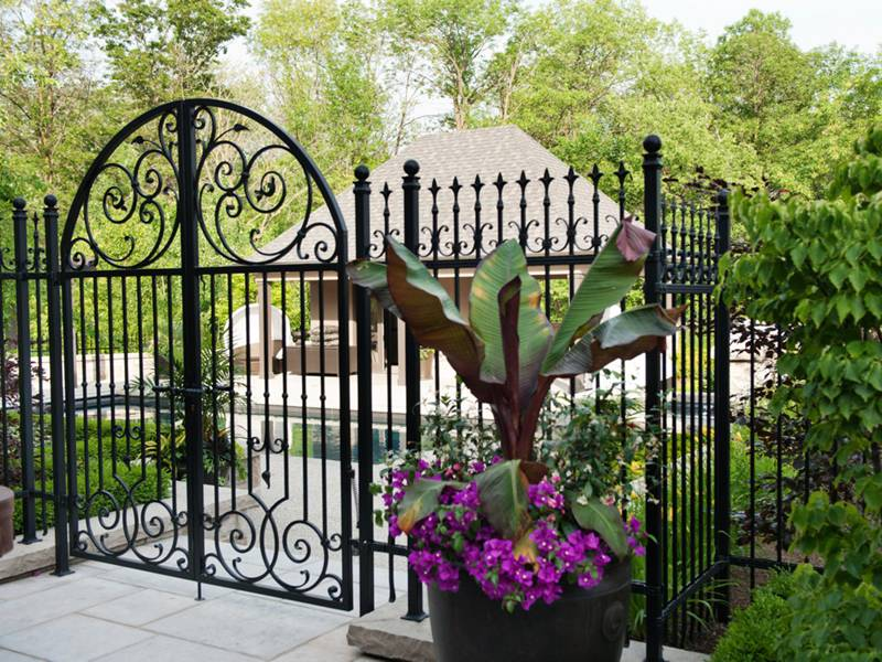 Private house is surrounded by patterned wrought fence as well wrought iron gate.