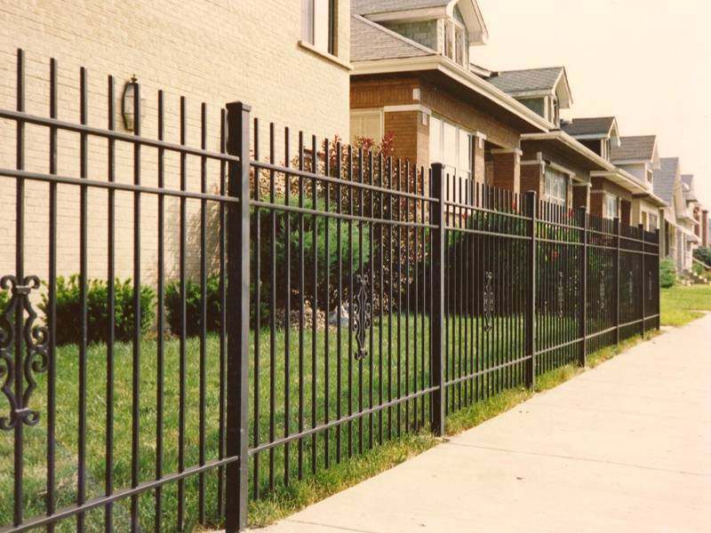 Wrought iron fence without finial around residential buildings.