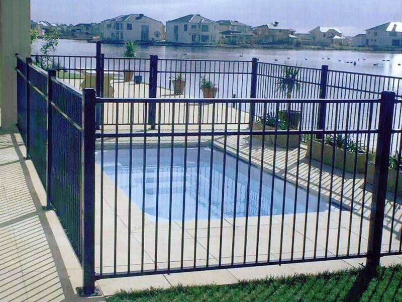 Wrought iron fence without finial around personal swimming pool.