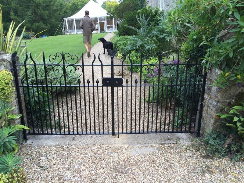 Wrought iron gate for a person garden, a man and his dog in the garden.