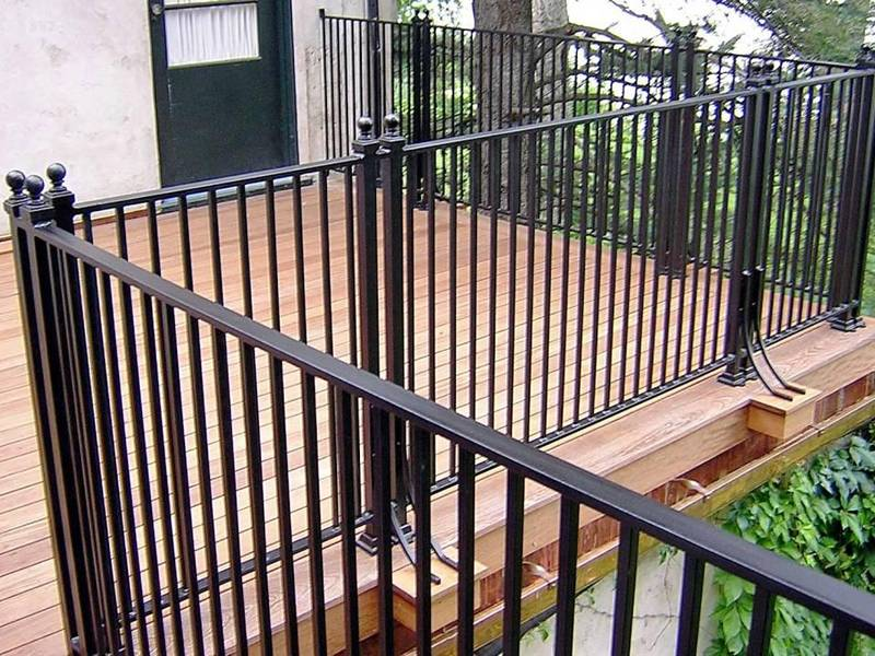Wrought iron railing fixed on the wood floor outside house.