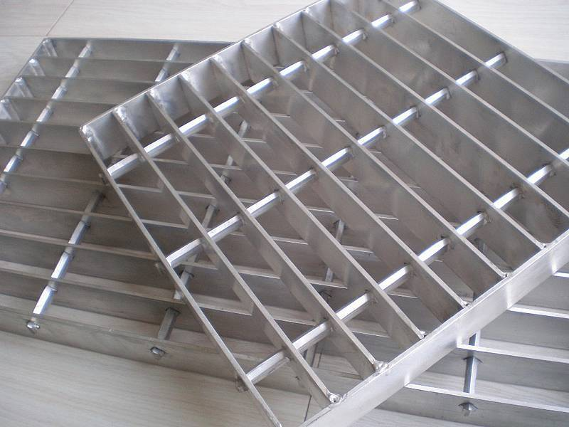 There are two galvanized swage locked gratings of different sizes placed together on the ground.