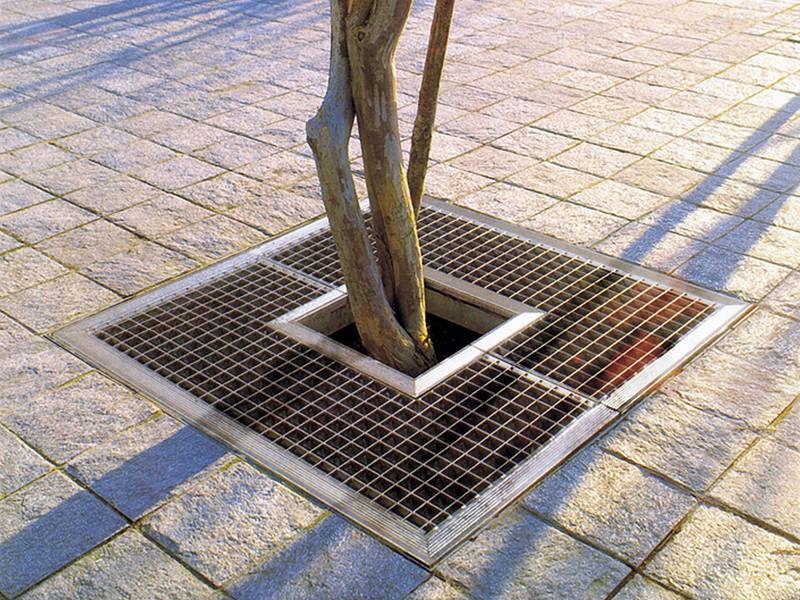 Steel bar grating used as tree cover surrounding a tree to protect the tree.