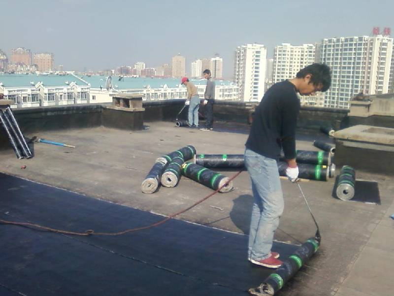 Three workers are repairing the roof with waterproof board.