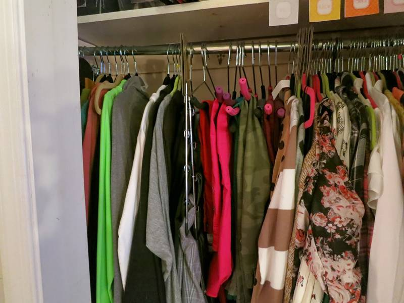 Wire hanger hanging a lot of clothes in wardrobe.