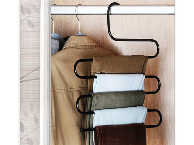 A black wire hanger hanging several pants.