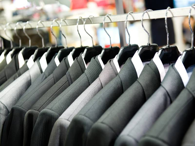 Wire hanger hanging a large amount of suits.